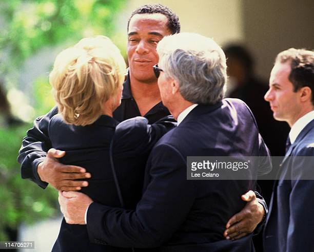 AC Cowling a friend of OJ Simpson hugs attendees as he departs the funeral for Simpson's exwife Nicole Brown Simpson June 16 1994