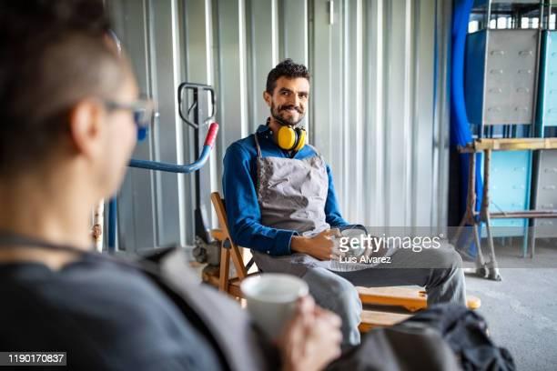 coworker taking coffee break in workshop - pause machen stock-fotos und bilder