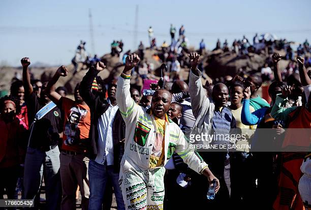 Coworkers and relatives of 34 miners shot dead by South African police during a violent wage strike sing and dance as they gather on August 16 2013...