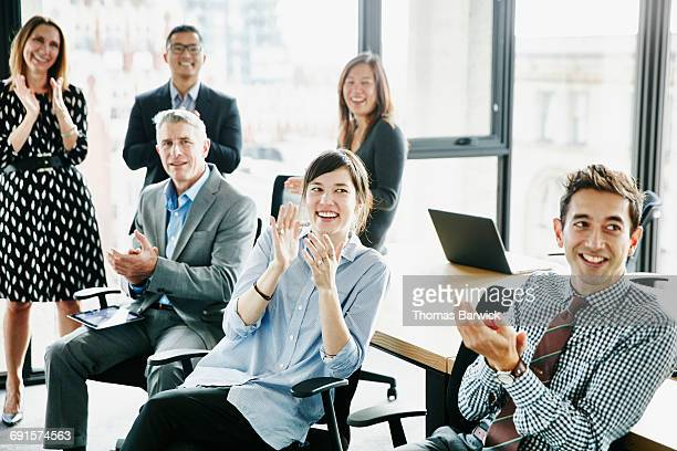 coworkers applauding after presentation in office - employee engagement stock pictures, royalty-free photos & images
