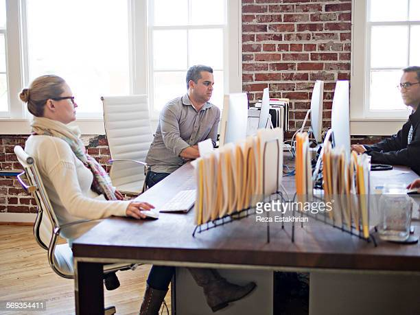 Coworkers at desk chat together