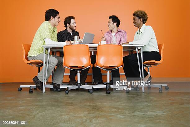 Co-workers at table in conference room, smiling