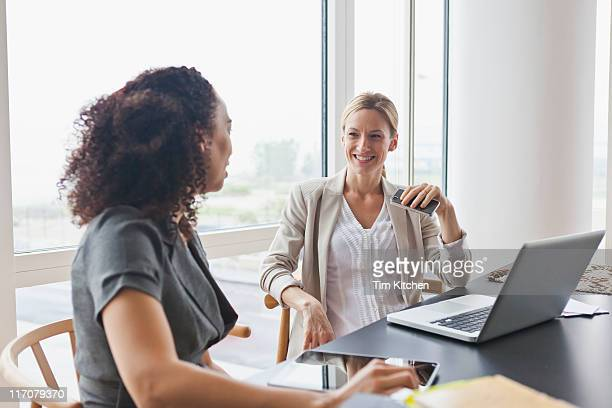 Coworkers at table with technology, talking