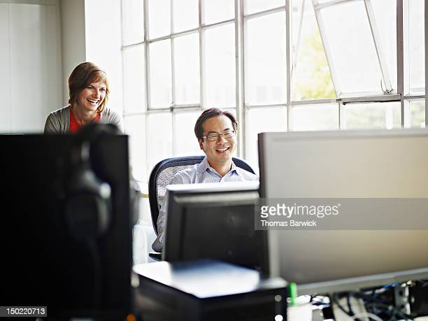 Coworkers at workstation in discussion in office