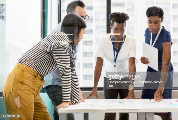 """co-workers brainstorming in modern office - """"compassionate eye"""" stock pictures, royalty-free photos & images"""