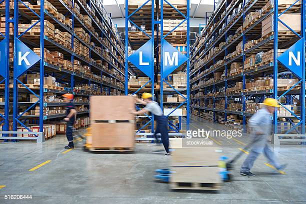 coworkers carrying cardboard box in warehouse. - heavy industry stock photos and pictures