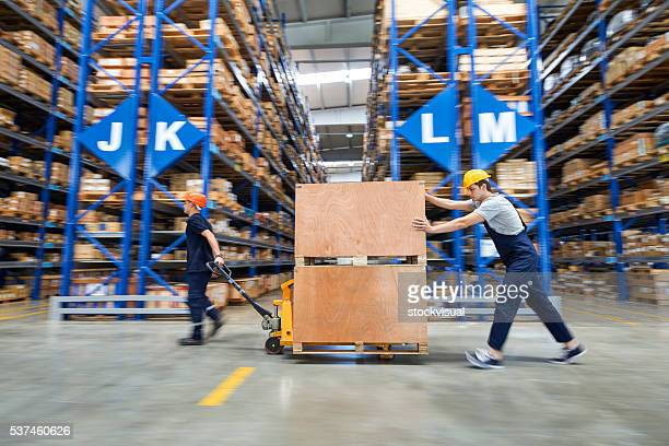 Coworkers carrying wooden box in warehouse.