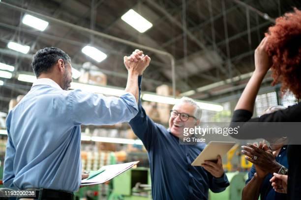 colegas de trabalho que comemoram alguma boa notícia em uma fábrica - parceria - fotografias e filmes do acervo