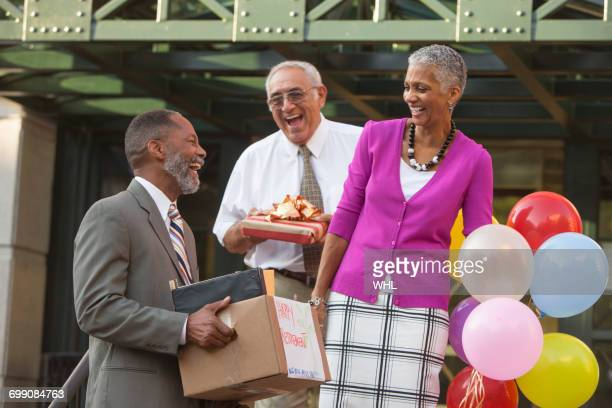 Co-workers celebrating with retiring man carrying belongings