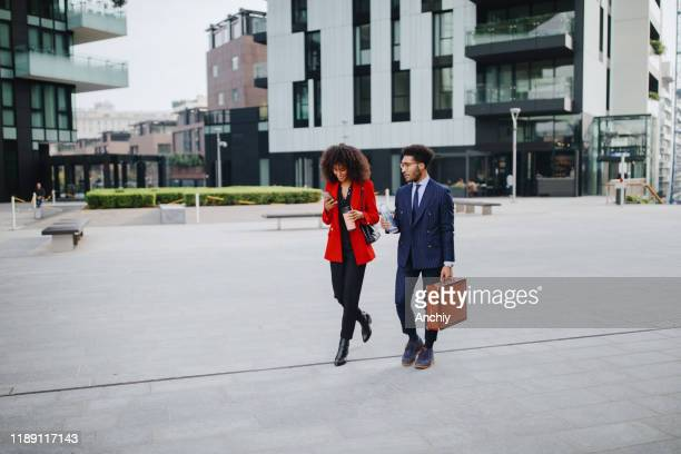 coworkers chatting while walking to their place of work - finance and economy stock pictures, royalty-free photos & images