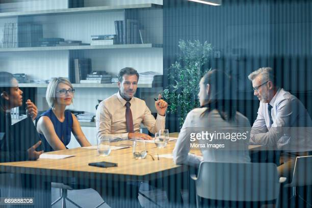 coworkers communicating at desk seen through glass - corporate business stock pictures, royalty-free photos & images