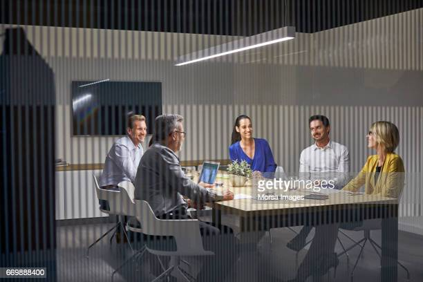 Coworkers communicating at desk seen through glass