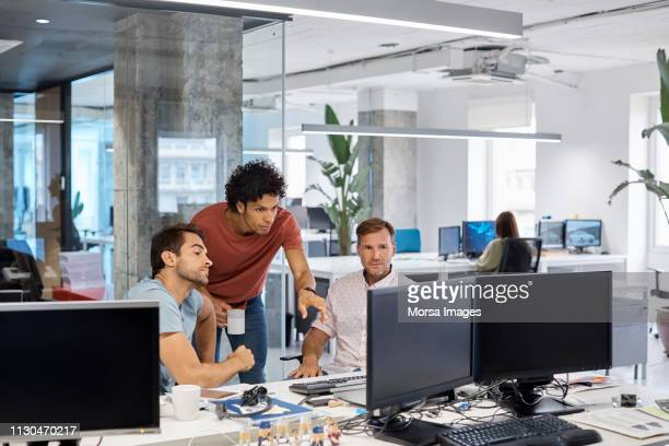 coworkers communicating while using computer - cloud computing stock pictures, royalty-free photos & images