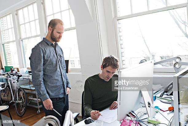 Coworkers discus ideas at office desk
