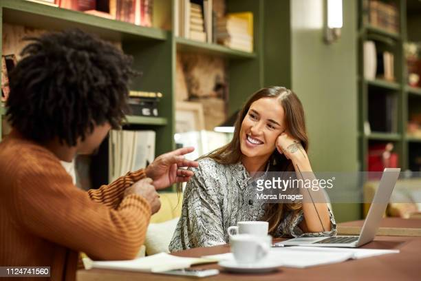 coworkers discussing at desk in creative office - cultures stock pictures, royalty-free photos & images