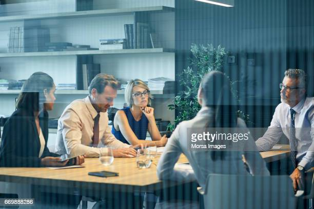 Coworkers discussing at desk seen through glass