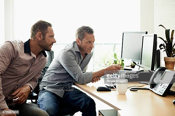 coworkers discussing data on computer - rolled up sleeves stock pictures, royalty-free photos & images