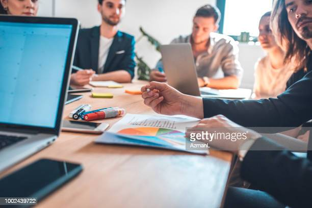 Coworkers discussing during meeting in office