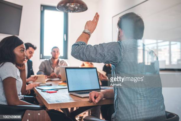 Coworkers discussing in board room during meeting