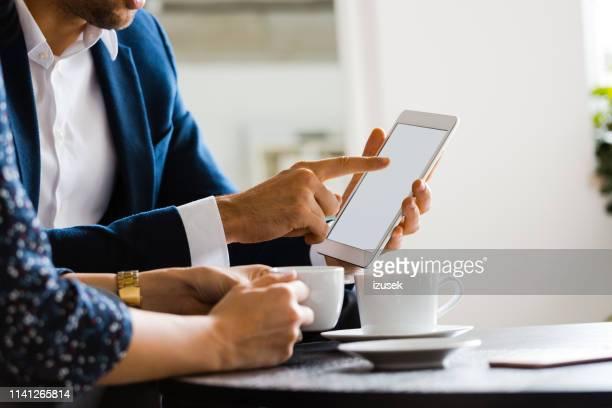 compañeros de trabajo discutiendo sobre tablet pc en la oficina - izusek fotografías e imágenes de stock