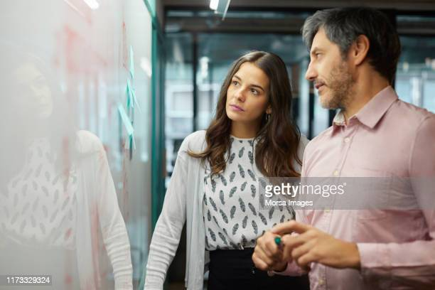 coworkers discussing over whiteboard in office - estratégia de negócio imagens e fotografias de stock
