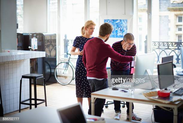co-workers discussing project at computer screen - joining the dots stock pictures, royalty-free photos & images
