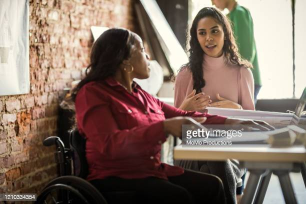 coworkers discussing project in architects office - disability stock pictures, royalty-free photos & images