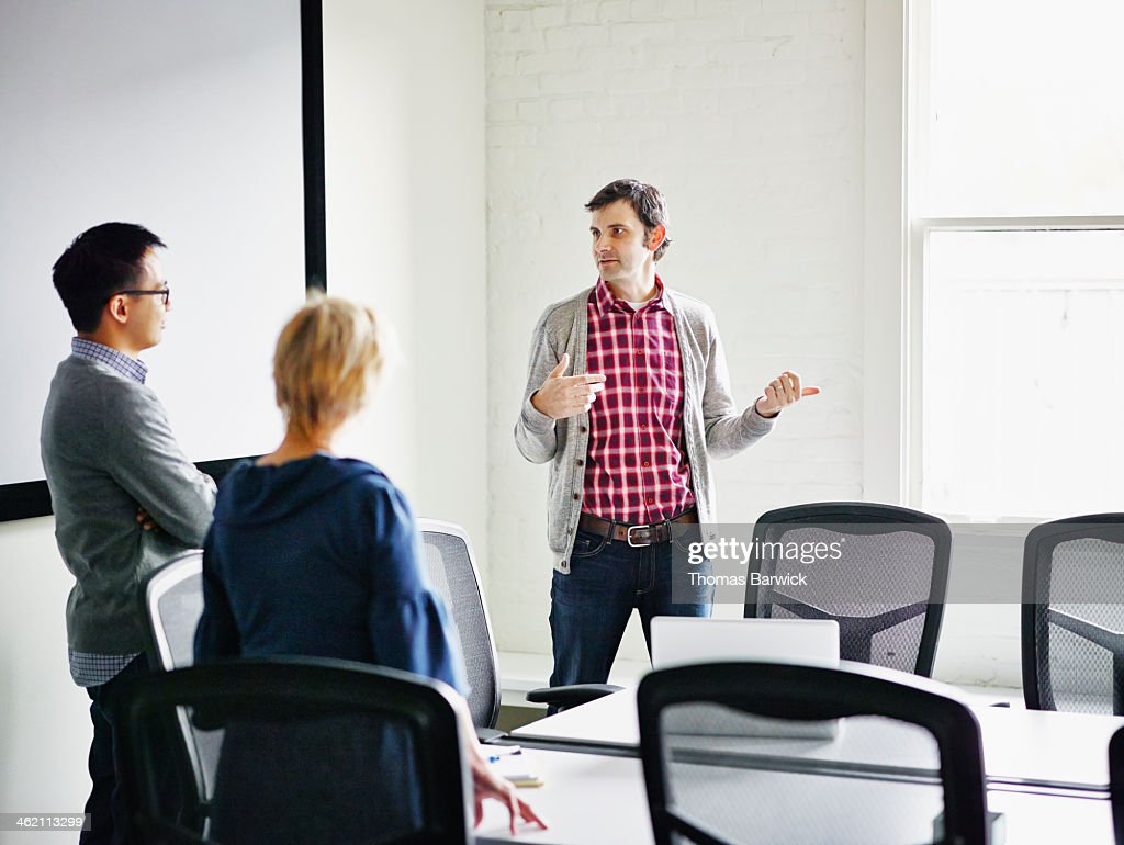 Coworkers discussing project in conference room : Stock Photo