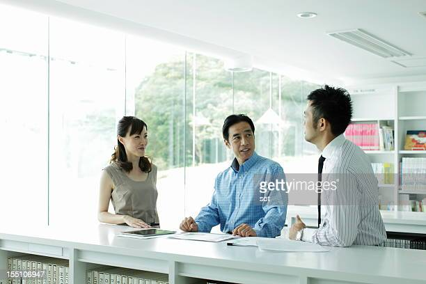 Coworkers discussing project in office library
