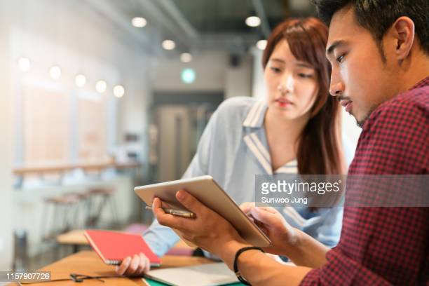 coworkers discussing project in office - asia stock pictures, royalty-free photos & images