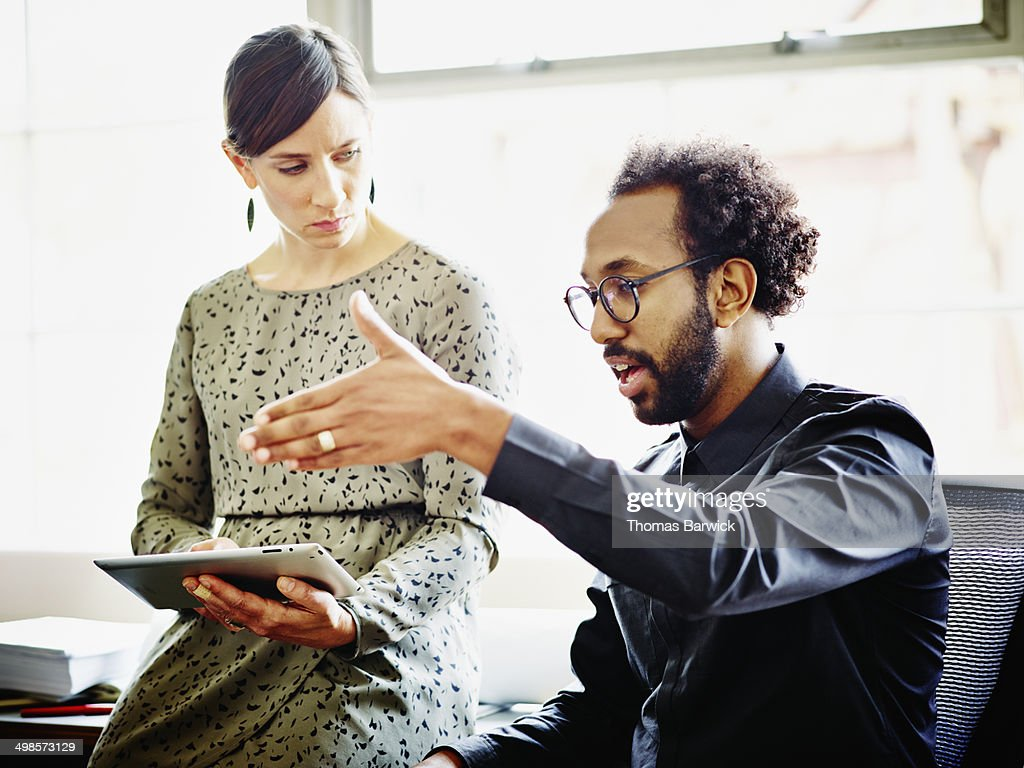 Coworkers discussing project in office : Stock Photo