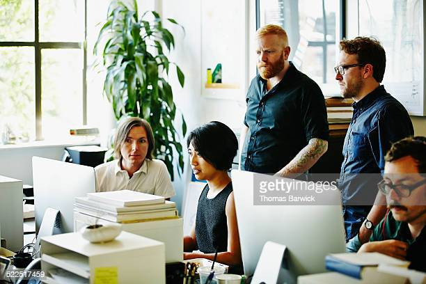 Coworkers discussing project on computer