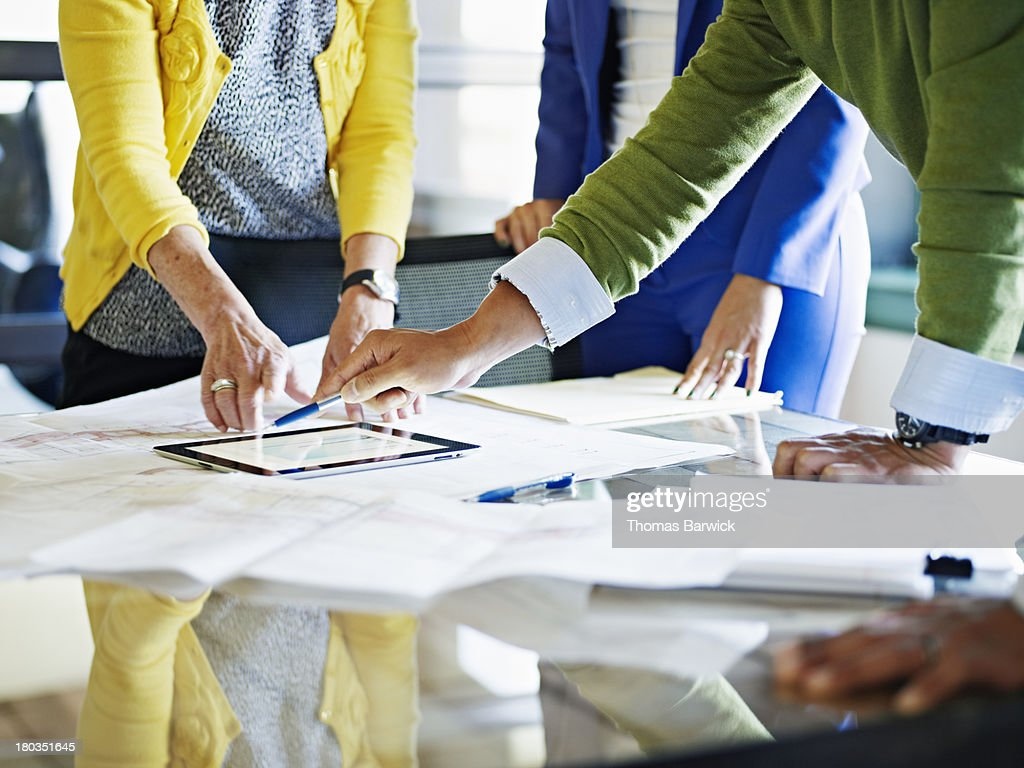 Coworkers discussing project on digital tablet : Stock Photo