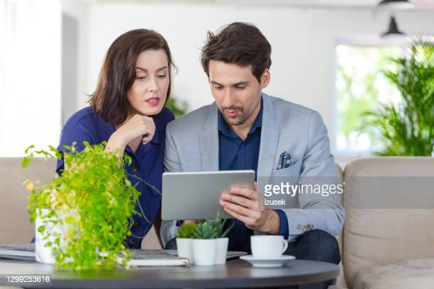 coworkers discussing project over digital tablet - mindzoom 2 stock pictures, royalty-free photos & images