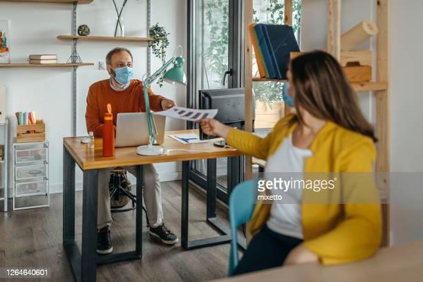 compañeros de trabajo haciendo papeleo en la oficina durante el brote de virus corona - devolución del saque fotografías e imágenes de stock
