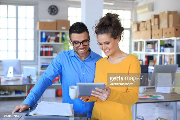 Coworkers drinking coffee and using digital tablet at workplace