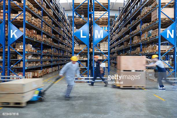 Coworkers driving manuel forklift in warehouse