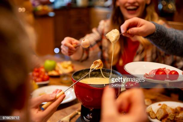 coworkers eating fondue - cheese stock photos and pictures