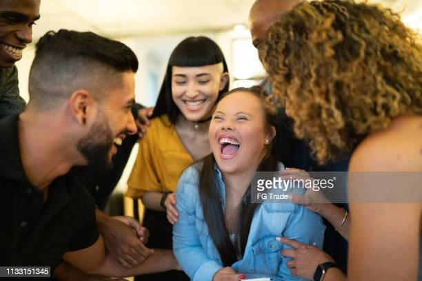 coworkers embracing a special needs businessperson at workplace - differing abilities female business stock pictures, royalty-free photos & images