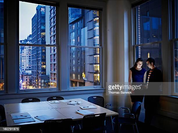 Coworkers examining digital tablet in office