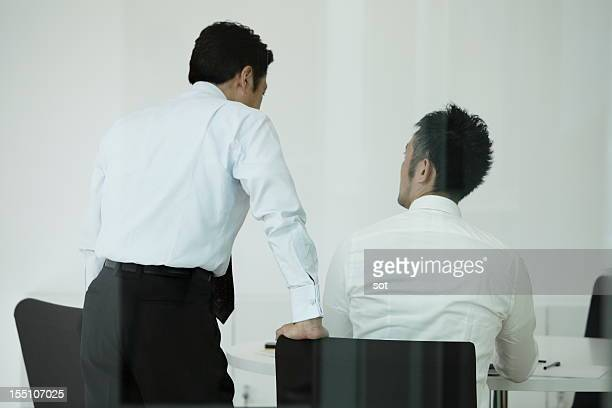 Coworkers examining plans in conference room