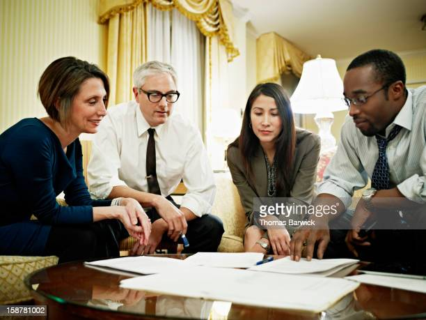 Coworkers examining project documents in hotel
