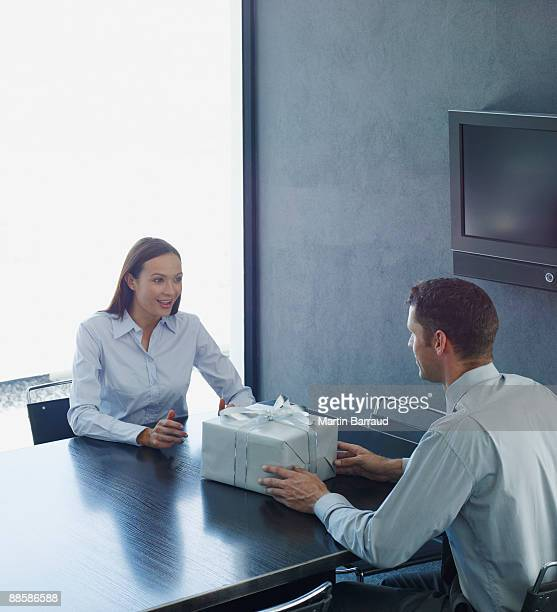 Co-workers exchanging gift in conference room