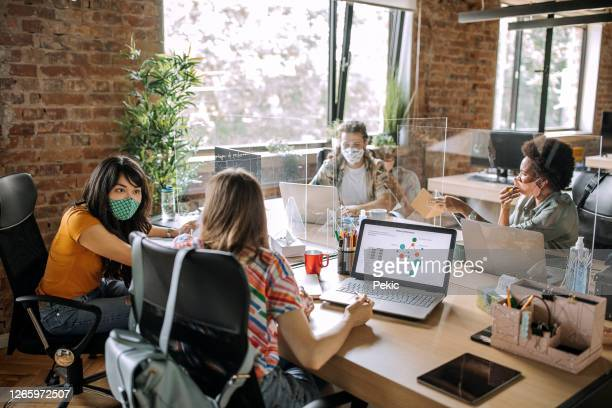 coworkers exchanging ideas at office during pandemic - alertness stock pictures, royalty-free photos & images
