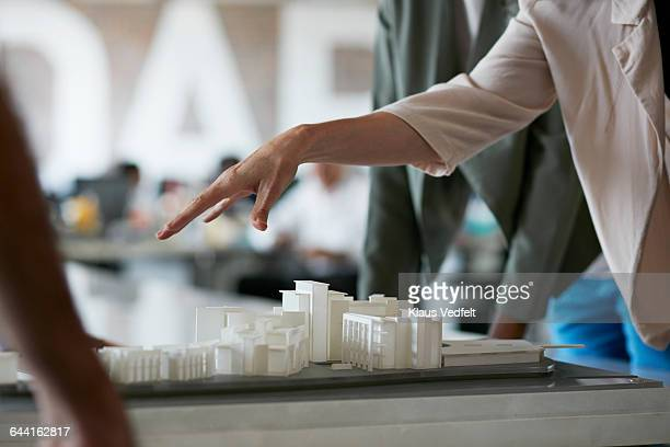 Co-workers gathered around architectural model