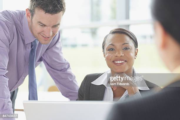 co-workers gathered around laptop - purple suit stock pictures, royalty-free photos & images