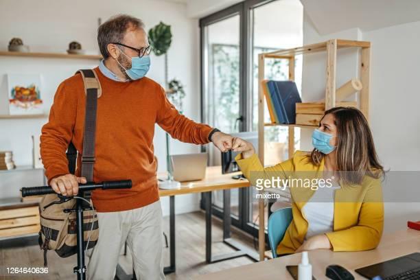 collègues se saluant les uns les autres avec la bosse de poing au bureau - éviter de se serrer la main photos et images de collection