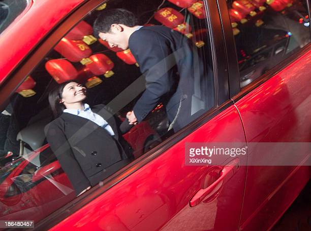 Coworkers handshaking next to the car at night, red lanterns on the background