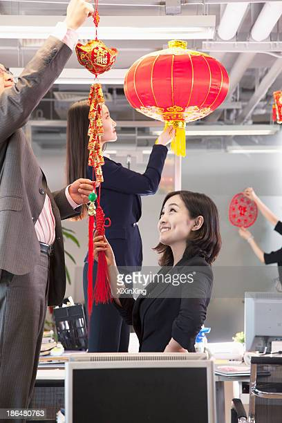 coworkers hanging decorations in office for chinese new year - chinese decoration stock pictures, royalty-free photos & images