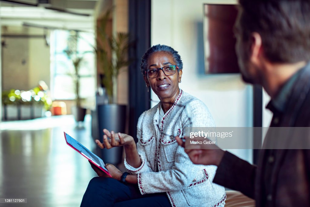 Coworkers having a meeting in the lobby : Stock Photo